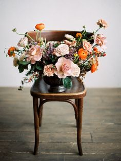 Loving the pops of orange in this whimsical, garden style floral arrangement. The way they combine with larger blush blooms and kind of spill in every direction is just enchanting! pink and orange flower arrangement   photo by Olga Siyanko