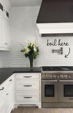 White Painted Brick Backsplash against Honed Black Granite Countertops