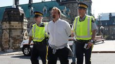 Police escort a protester at a rally against the Keystone XL pipeline on Parliament Hill in Ottawa on Monday, Sept. 26, 2011.