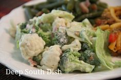 Next Day Salad - a layered salad made with iceberg lettuce, cauliflower, broccoli, red onion, bacon and Parmesan cheese, dressed with a vinegar and mayonnaise, mustard dressing and refrigerated for 12 to 24 hours, before serving.