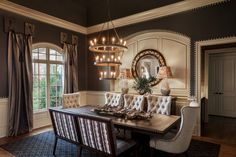 A very classic dining room with a luxurious feel showcasing mismatched chairs and an intricate dining table lit by a thr Orange Dining Room, Warm Dining Room, Pink Dining Rooms, Dark Wood Dining Table, Dining Table Lighting, Classic Dining Room, Minimalist Dining Room, Dining Room Colors, Elegant Dining Room