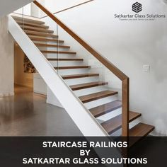 A blond-toned wood staircase railing graces the top of glass panels in this elegant modern staircase. It gives the space a seamless look. It is simple, beautiful, and sophisticated—the highlight of the room. #ModularGlassRailing #GlassRailing #interiordesign #gurgaoninteriordesigner #railingsystems #OfficeGlassRailing #ModularGlassRailing #GlassRailing #glassrailings #glassrailingsystems Modern Staircase Railing, Wood Railings For Stairs, House Staircase, Stair Railing Design, Home Stairs Design, Interior Staircase, Door Design, Glass Stair Railing, Modern Stairs Design