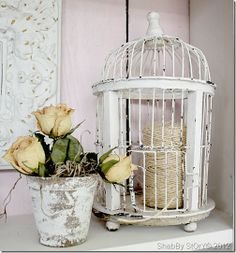 A bird cage to hold twine... plus other beautiful helps inside a pink garden cabinet... gorgeous! By Shabby Story