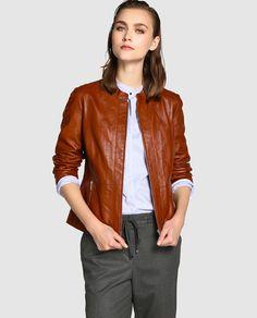 Cazadora básica, realizada en piel en color marrón. Con cuello redondo y cierre y bolsillos con cremallera.
