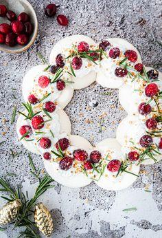 Bij pavlova denk je waarschijnlijk niet direct aan vegan!  Met dit recept kun je tijdens de kerst een spektakel stuk van een dessert op tafel zetten 🎄.   De voorbereiding kost slechts 15 min, daarna moet hij nog wel een paar uurtjes in de oven. Door de cranberry's en rozemarijn ziet deze pavlova er heel feestelijk uit! Pavlova, Floral Wreath, Vegan, Desserts, Decor, Tailgate Desserts, Floral Crown, Deserts, Decoration
