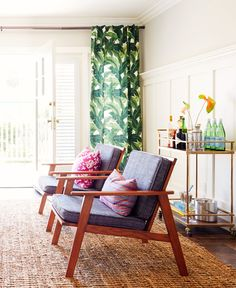 Two wood armchairs with colorful cushions and patterned curtains in living room with gold bar cart