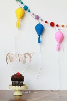 Fun birthday decor idea: make this balloon bunting by filling balloons with foam and tying with colorful twine! Inexpensive birthday decor idea! Fun birthday balloon tutorial!
