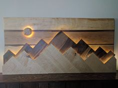 Wood mountain range wall art.  The sun/moon functions as a dimmer switch for the lights behind the mountain ranges and the sun/moon.  The backboard is cherry with strips of black walnut, the rear mountain range is figured black walnut, the front mountain range is figured white maple and the sun/moon is white maple.