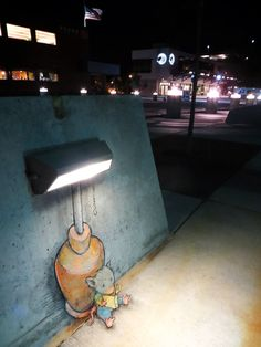 Mouse reading a book under the street lamp - chalk artwork by David Zinn