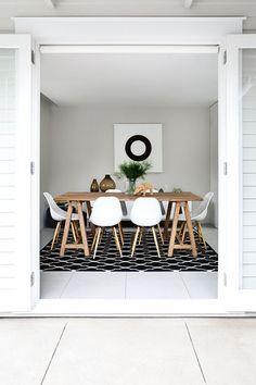 white eames chair, rustic table, dark rug