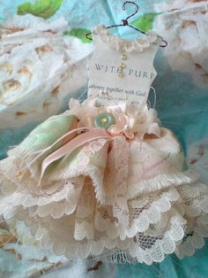 Wire, lace & paper. Would make pretty tea party invites. Looks like dolls house hangers are used.