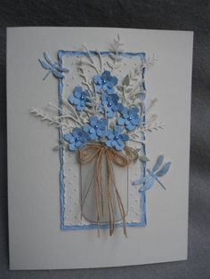 Blue flowers in mason jar, lacy foliage, blue dragon flies, lacy bouquet in blue Heavy ivory card stock Swiss dot embossing folder Swiss dot background edged with blue and frayed edging on both Two blue dragonfly dance around the bouquet Blue flowers all have pearl centers~ photo is a
