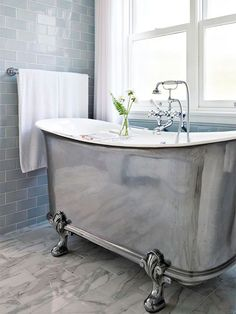 a stunning metallic claw foot tub with a vintage feel