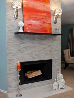 This blue and neutral mosaic tile fireplace is a charming accent to this living room. A bold orange painting placed on the mantel brightens up the space.