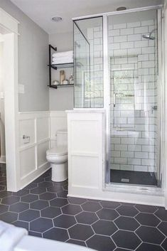 We used large, hexagonal flooring throughout the whole bathroom. I love the way it paired with the classic white subway tile we used in the shower. remodel A Master Bathroom Renovation Bathroom Grey, Bathroom Renos, Bathroom Flooring, Bathroom Vanities, Bathroom Cabinets, Subway Tile Bathrooms, Design Bathroom, Bathroom Shelves, Dark Floor Bathroom