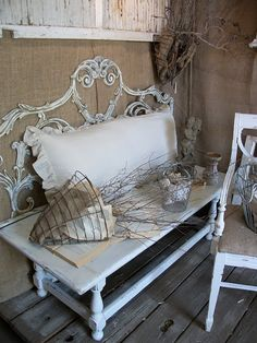 Looks like a sweet iron bench...but I think it is a headboard and table/old door.....soooo cute! Love the old newspapers in sconces with twigs!