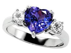 Heart Shape Tanzanite Diamond Engagement Ring - The traditional symbol of love can be represented with any color and there's no exception with this lovely Heart Shape Tanzanite Diamond Engagement Ring stamped in 925 Sterling Silver placed within a Prong setting featuring a Tanzanite Heart cut center stone along with two mid size White Round cut accent sides stones on both sides of the shank. The Heart Shape Tanzanite Diamond Engagement Ring is Cubic Zirconia and all of the diamonds are…
