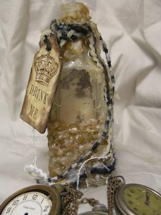 Alice in a bottle    Mixed Media Alice in antique glass bottle, with beeswax stamping and vintage lace.