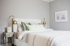 A quiet and relaxed bedroom was achieved by painting the walls a light gray and choosing a slightly colder — almost purple — shade for the drapes. Source: Design by Homepolish West Coast Creative Director Orlando Soria and photography by Tessa Neustadt for Homepolish