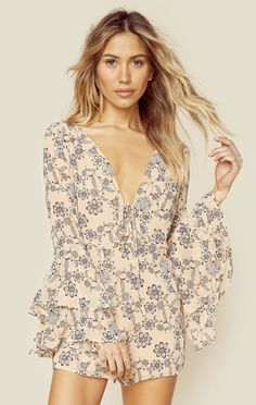 The For Love and Lemons Pia Romper features a deep v neckline with lace up detailing, long ruffled bell sleeves, and a floral print throughout. This little number is a spring essential!