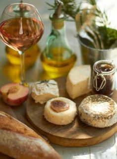 Wine  Cheese Taste - round cheeses on a rustic board, crusty bread, olive oil and a crisp and delicious rosé wine