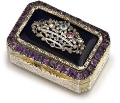 A SILVER-GILT AND 'GEM'-SET SNUFF-BOX  20TH CENTURY, STAMPED '800'  Oblong with canted corners, the hinged cover set with a lapis lazuli panel, set with a silver and 'gem' set basket of flowers, all within a purple stone border, the sides and base engraved with foliage. FROM THE COLLECTION OF S.A.R. LA PRINCIPESSA REALE MARIA GABRIELLA DI SAVOIA.