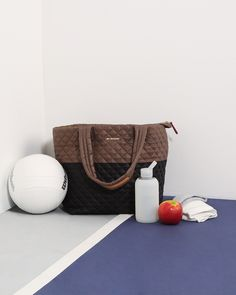 Black and fawn Medium Metro Tote on a workout with a bkr bottle on a volleyball court