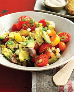 A light and delicious corn salad. Ingredients  1 ear corn (husk and silk removed; tip cut off) 2 pints cherry, grape, or pear tomatoes, halved (or quartered if large) 1 avocado, halved, pitted, peeled, and diced 2 scallions, thinly sliced 2 tablespoons fresh lime juice 1 tablespoon vegetable oil, such as safflower Coarse salt and ground pepper
