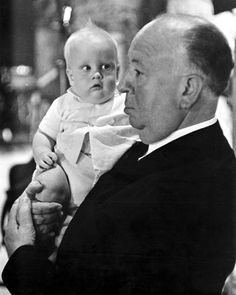 Alfred Hitchcock and a baby on the set of The Birds (1963).
