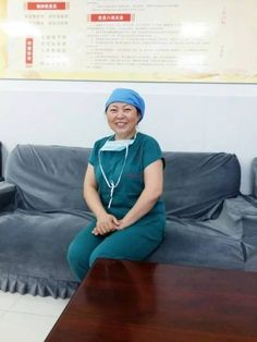Kneeling nurse lifts lamp to help save patient