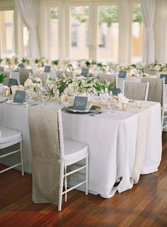 These simple yet elegant chair covers are draped over Chiavari chairs; they feature subtle button details behind the cushion. The soft, taupe hue adds warmth to an otherwise all-white reception tablescape.
