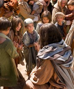 Jesus Christ, surrounded by a group of children, shows them love and compassion.