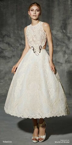 Short ivory wedding dress made of different types of natural fibers crochets. Ankle-lenght bridal trend skirt with high volume, a different wedding look for modern brides. The top and skirt are joined by a 24K golden ring. Highlights beautiful open back neckline.