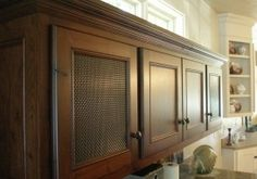 The bronze wire mesh has been darkened to blend with the dark walnut cabinetry.