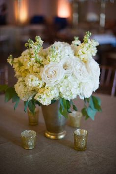 White floral centerpiece with candles for wedding reception. M. Elizabeth Events