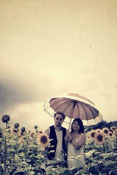 Couple Portrait of a folk duo in a Sunflower Field in July.