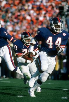 Joe Morris of the New York Giants carries the ball led by Maurice Carthon against the Denver Broncos during Super Bowl XXI on January 26 1987