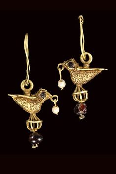 Iran or Fatimid Egypt   Pair of gold earrings; each in the form of a small bird with garnet inset eyes, a pendant seed-pearl hanging from the mouth, the wings forming a heart-shaped panel on the back, each standing on an open wire-work roundel above a pendant garnet, suspension loop above   ca. 11th century   3'120£ ~ sold (Oct '06)