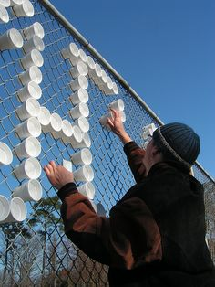 Hundreds of styrofoam cups are transformed into typography when arranged in a chain-link fence.