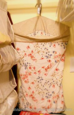 An old wire hanger and pillow case can be used to make a hanging laundry hamper!