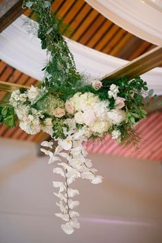 Hanging floral ceiling feature.  Flowers were placed on four corners of an oversized hanging frame.  Created by Akiko Floral Artistry.  Photo Credit:  Milton Photography.  #phalaenopsis #orchids #blush #gold #blushandgold #ivory #tulips #roses #peonies #hydrangea #hangingflowers #goldframe #frame