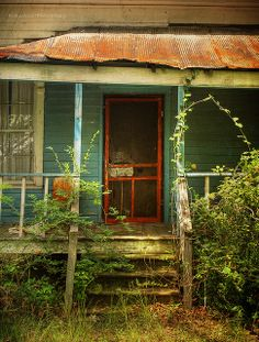 Old farmhouse...porch..railings and steps ...love the rusty tin roof and screen door.  Lots of sweet memories made here....