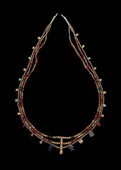Necklace; three strands separated in center by a long vertical gold bead. The two upper strands of small gold, carnelian, and blue glass balls; lower strand of small gold balls and pendants of gold, amazon stone, and blue glass. At each end three gold tubular beads.