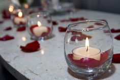 Votive candle holders with red rose petals in the bottom, underneath the candlevendors: An Impressive Event