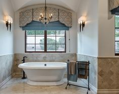 In the corner of this master bath, a freestanding bathtub offers a place to relax and unwind after a long day's work. Window light as well as a pair of sconces and a chandelier above the bathtub ensure the space is well lit.