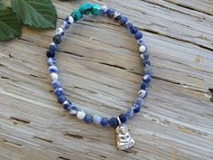 """$38 - BUDDHA'S WISDOM BRACELET    """"The only real failure in life is not to be true to the best one knows."""" -Buddha  This matte sodalite and turquoise nugget bracelet is a gentle year-round reminder to live in an om-azing life.  Buddha charm is made of sterling silver.  Stretch bracelet measures 7"""", sized to fit most wrists."""