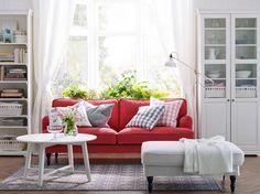 Salón blanco con sofá STOCKSUND rojo, armario y librería LIATORP blancos,  y solución de almacenaje también blanca.
