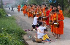 https://flic.kr/p/EFpMzi   Side street in Luang Prabang, Laos (Tak Bat morning alms collecting procession)   Traditionally in Laos males would become novice monks at some point in their lives, giving them the opportunity to gain both an education and religious merit. Laos also has a somewhat unique belief among Buddhist countries that merit (boun) is transferrable among people, thus a son or daughter may make merit for a parent by temporarily entering a monastery. Lay persons are expected…