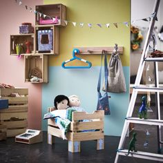 Wooden crates in a colourful children's room used as a doll's bed and wall storage.