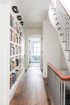 una estantería estrecha desde el suelo hasta el techo a lo largo de un pasillo, pintada en blanco a juego con la carpintería para que resulte visualmente ligera